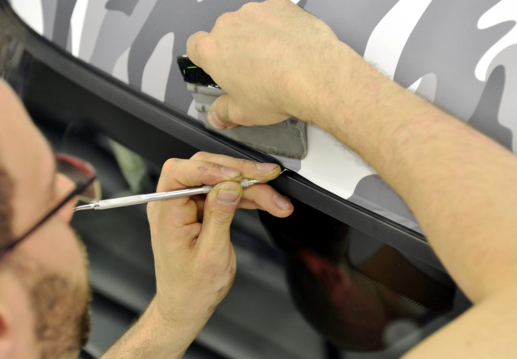 A vehicle wrapping specialist working with precision on a car